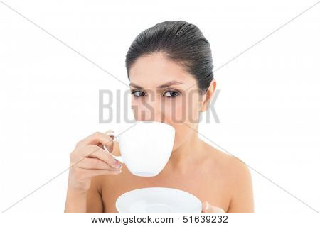 Pretty brunette holding a cup and saucer and taking a sip on white background