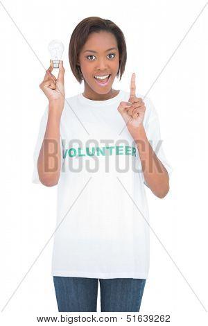 Woman holding light bulb raising the finger up on white background
