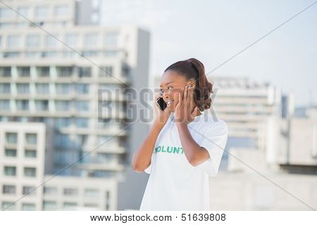Cheerful altruist woman on the phone covering her ear outdoors on urban background