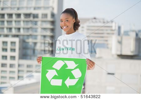 Happy altruist woman holding recycling sign outdoors on urban background