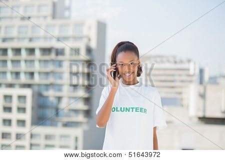 Cheerful altruist woman on the phone outdoors on urban background