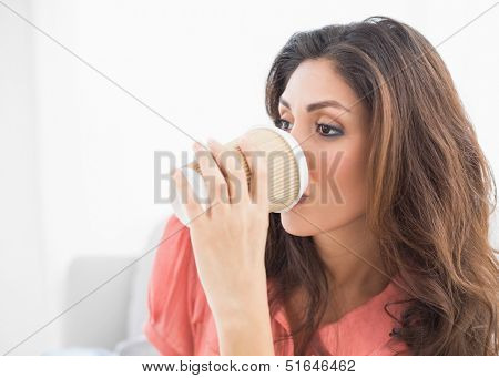 Smiling brunette sitting on her sofa sipping from disposable cup at home in the sitting room