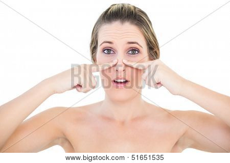 Shocked woman pressing blackhead on her nose posing on white background