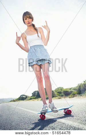 Young woman making rock and roll gesture while balancing on her skateboard on a deserted road
