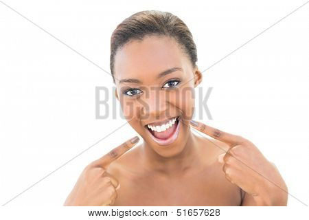 Smiling natural beauty pointing at her smile on white background