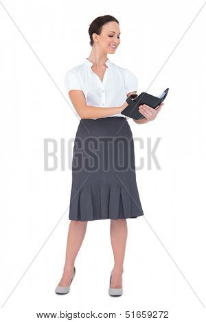 Happy businesswoman holding her datebook on white background