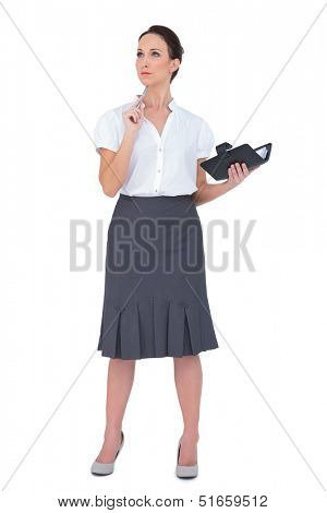 Pensive businesswoman holding datebook on white background