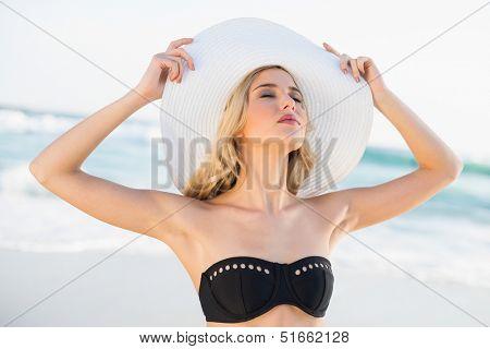Relaxed sexy blonde in elegant bikini wearing straw hat posing on a beautiful sunny beach