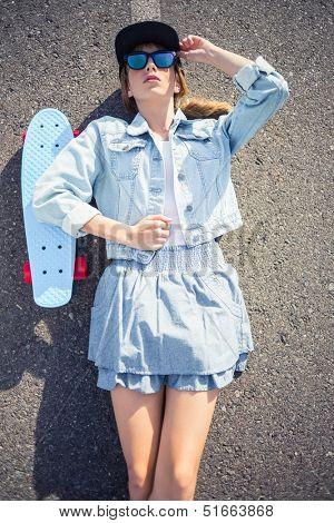 Rebellious blonde skater lying on the highway in summertime