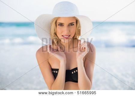 Happy sexy blonde in elegant bikini wearing straw hat posing on a beautiful sunny beach