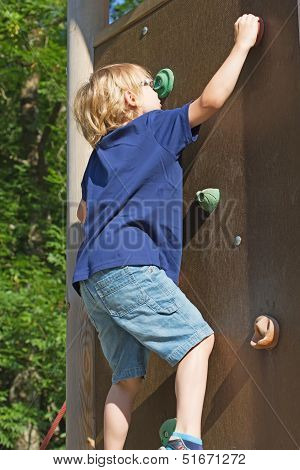 The Blond Boy Climbs The Climbing Wall.