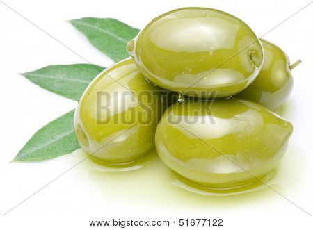 Green olives with leaves in oil isolated on a white.