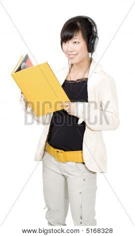 Asian Woman With Yellow Book And Headphones