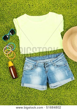 Top, shorts and beach items on bright green background