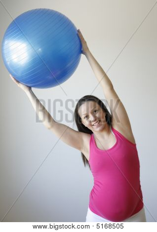 Young Smiling Pregnant Woman Exercising With Fitness Ball.