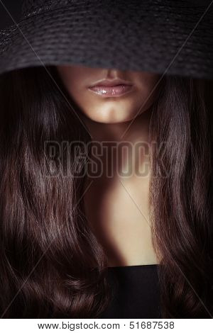 Young beautiful woman with long hair in dark, studio shot