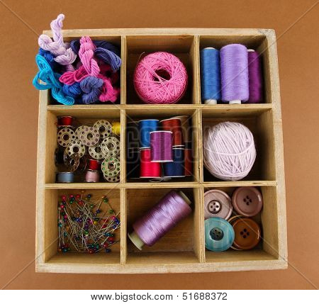 Thread and materials for handiwork in box on brown background