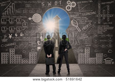 Two Businesspeople Looking Through Key Hole