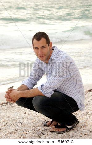 Modelo masculino guapo agazapado en la playa mirando el visor