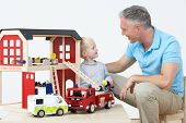 picture of fire-station  - Teacher And Pupil Playing With Wooden Fire Station - JPG