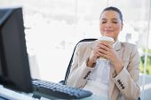 Happy sophisticated businesswoman smelling coffee in bright office