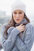 Shivering cute woman with winter clothes on posing outdoors on a cold grey day