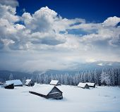 Winter mountain landscape with wooden huts and fresh snow. Carpathian mountains, Ukraine