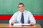 Portrait of happy mature male teacher sitting with binder and pen at desk in classroom