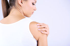 picture of shoulder-blade  - Pain in blades the girl on gray background - JPG