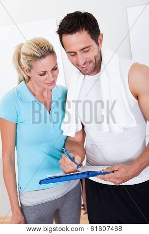 Fitness Instructor Taking Notes After A Session