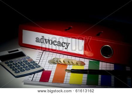 The word advocacy on red business binder on a desk