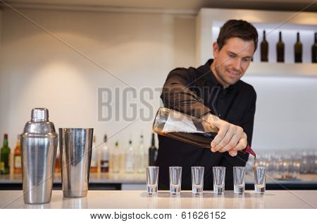 Happy bartender pouring cocktail into shot glasses at the bar