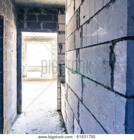 Corridor of grey large brick walls