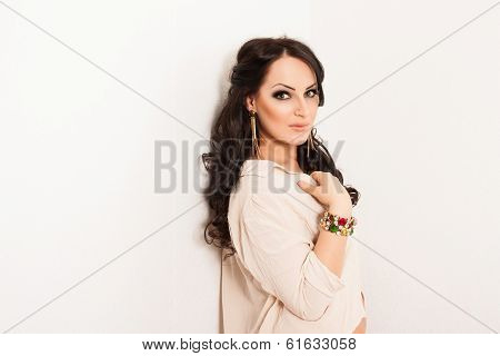 Elegant fashion woman with jewelry and a shirt near white wall.