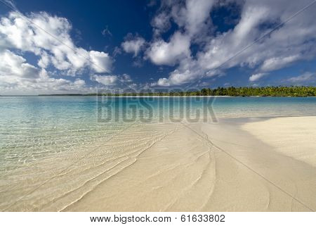 Sandy, shallow, tropical water with palm tree island in the distance. One Foot Island, Aitutaki