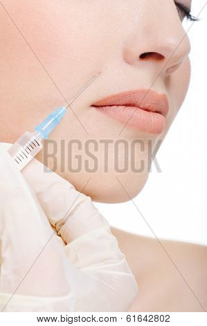 Doctor giving a shot on female cheek - fragment of face
