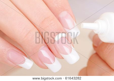 Woman caring of her finger applying the moisturizing cosmetic cream on fingernail