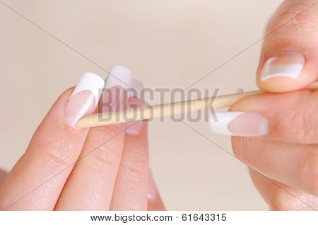 Female cleaning cuticle on hands with a cosmetic stick - macro shot and soft focus