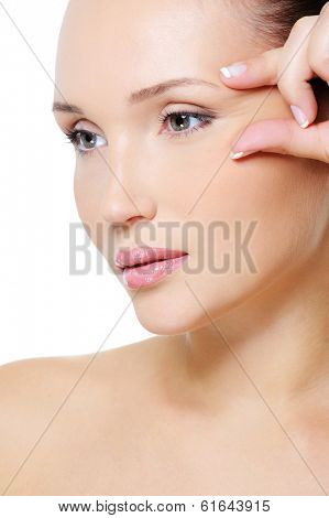 Close-up face of an young beauty  woman squeeze skin near her eye