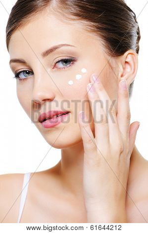 Beauty female applying cosmetic cream on skin around eyes - isolated on white