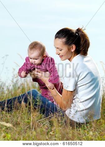 Happy young mather with baby outdoor siting on grass