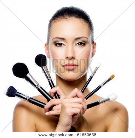 Beautiful woman with makeup brushes near her face - isolated on white