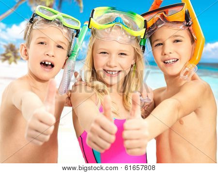 Portrait of the happy children with thumbs-up gesture at beach.  Schoolchild kids standing together in bright color swimwear with swimming mask on head .