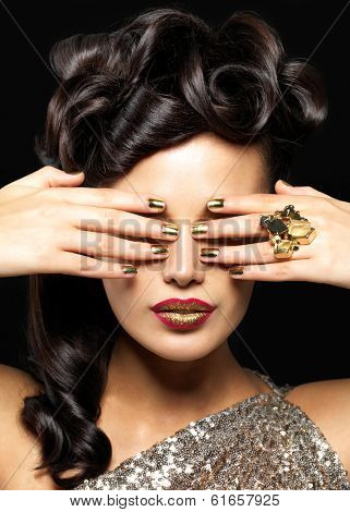 Beautiful  woman with golden nails and creative lipstick. Brunet girl model with style hairstyle on black background