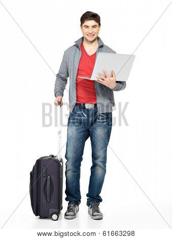 Full portrait of young smiling happy man with suitcase and laptop- isolated on white