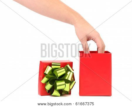 Red gift box with a hand on it.