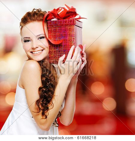 Happy young woman with birthday present in hands posing indoors