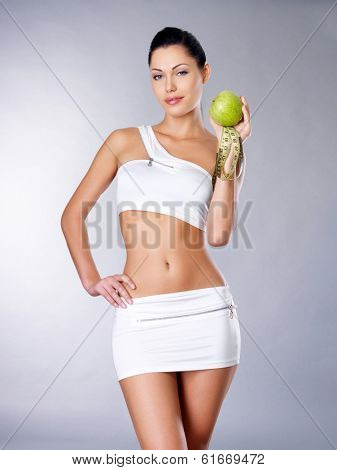 Healthy girl with apple and measuring tape. Healthy lifestyle cocnept.