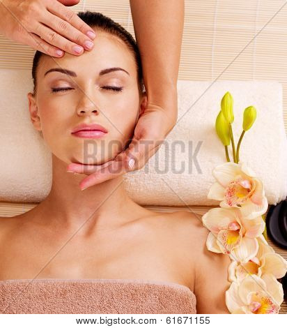 Masseur doing massage the head of an adult woman in the spa salon