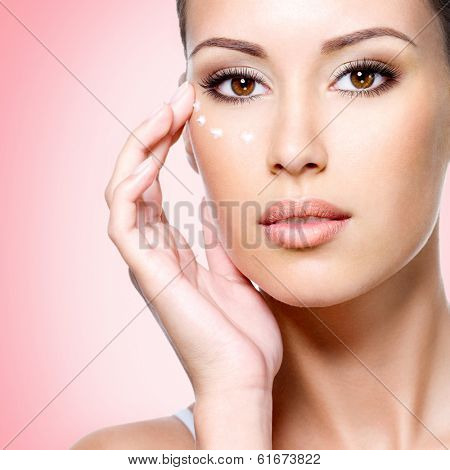 Portrait of woman with healthy face applying cosmetic cream under the eyes